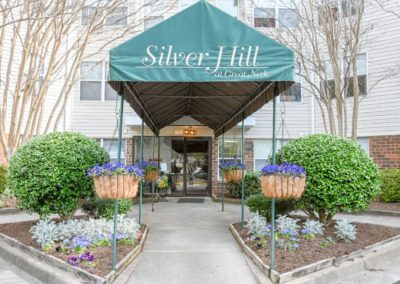 a green awning that says Silver Hill at Great Neck